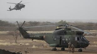 Un helicóptero francés Puma se posa en una base de las Fuerzas Armadas de Malí al lado de un helicóptero Caimán que vuela en una toma del 27 de marzo de 2019.