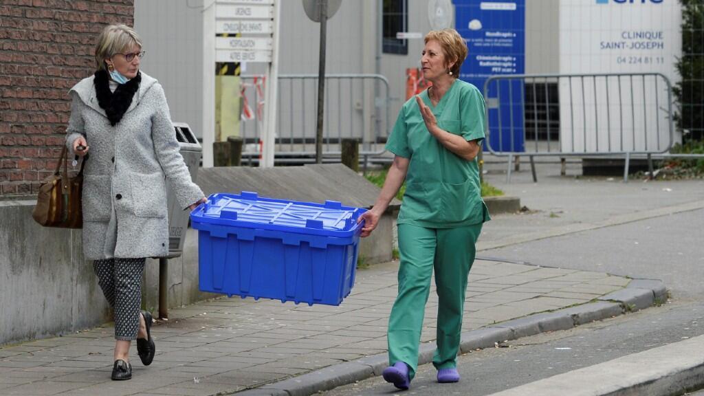 Dos mujeres ayudan al traslado de un hospital a unas instalaciones mayores en Liege, Bélgica, el 20 de marzo de 2020.