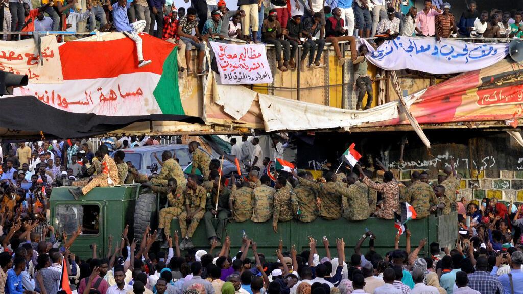 Un camión militar pasa a través de los manifestantes que asisten a una protesta frente al Ministerio de Defensa en Jartum, Sudán, el 14 de abril de 2019.