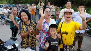 Espectadores saludan mientras una de las ambulancias que transporta a los escolares rescatados sale del aeropuerto militar en Chiang Rai, Tailandia, el 10 de julio de 2018.