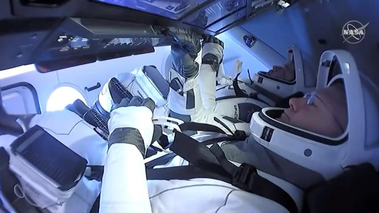 Los astronautas Robert Behnken y Douglas Hurley aparecen a bordo de la nave espacial Dragon Endeavour de SpaceX, el 2 de agosto de 2020, en esta captura de pantalla tomada de un video.