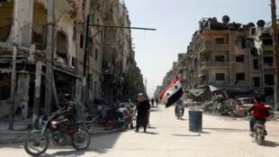 Una bandera de Siria ondea en medio de una calle dañada en la ciudad de Duma en Damasco, Siria, el 20 de abril de 2018.