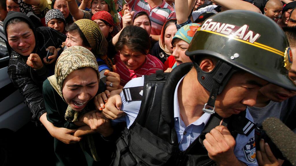 Una mujer sostiene a un policía chino mientras una multitud de lugareños se enfrentan a las fuerzas de seguridad en Urumqi, capital de Xinjiang, durante unas protestas en 2009.