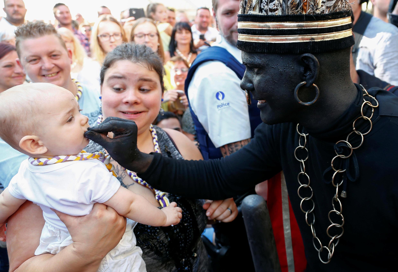"""""""El salvaje"""", un intérprete blanco disfrazado de negro, toca a un bebé durante el festival Ducasse d'Ath, en la ciudad occidental de Ath, Bélgica 25 de agosto de 2019"""