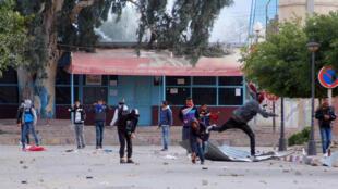 Des manifestants jetant des pierres en direction de la police, mercredi 20 janvier, à Kasserine.
