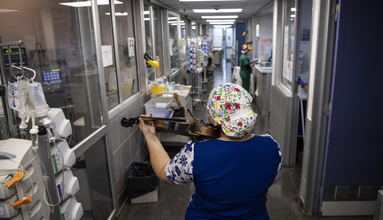 La enfermera chilena Damaris Silva toca el violín para los pacientes infectados con COVID-19, en la Unidad de Cuidados Intensivos del hospital El Pino, en Santiago de Chile, el 9 de julio de 2020.