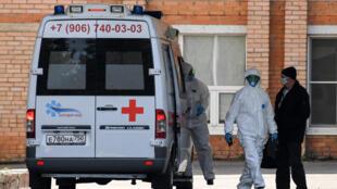 Des soignants près d'une ambulance garée dans un hôpital où des patients infectés par le Covid-19 sont traités, à Khimki, près de Moscou, le 3 mai 2020.