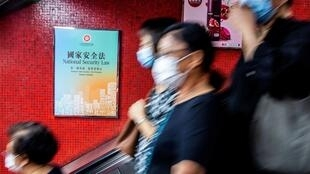 A government advertisement (L) promoting China's national security law is displayed inside an MTR train station in Hong Kong