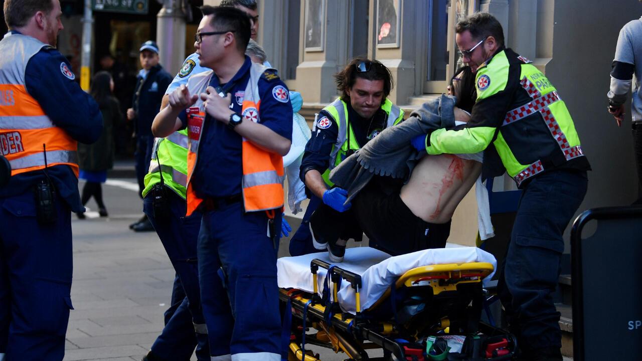 Paramédicos trasladan a una mujer herida con arma blanca en el centro de Sídney, Australia, de que el agresor fuera detenido el 13 de agosto de 2019.