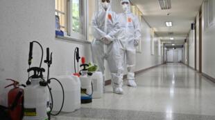 مسؤولان في قطاع الصحة  يستعدان لتعقيم صف في مدرسة ثانوية في سيول في 11 أيار/مايو 2020.