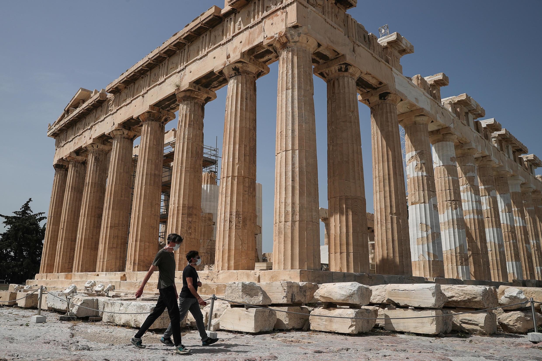الزوار يرتدون أقنعة واقية يتنزهون بمعبد بارثينون حيث تم إعادة فتح موقع أكروبوليس الأثري للزوار، في أثينا، اليونان، 18 مايو/ أيار 2020.