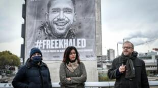 Le secrétaire général de Reporters sans frontières (RSF) Christophe Deloire (g), la chanteuse algérienne Souad Massi (c) et le street artiste Guemy alias C215 devant une bâche géante à l'effigie du journaliste algérien Khaled Drareni condamné à deux ans de prison ferme, le 15 octobre 2020 à Paris
