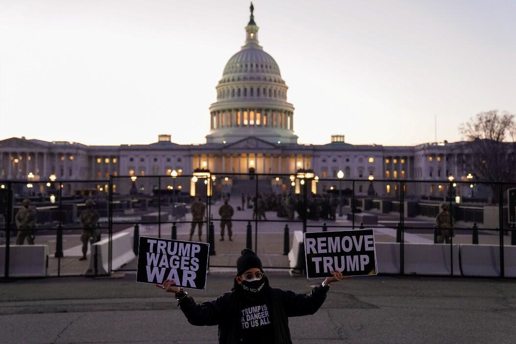 A protester with banners in favor of the impeachment of President Donald Trump, in front of the Capitol, the seat of the United States Congress.  In Washington DC, USA.  USA, January 12, 2021.