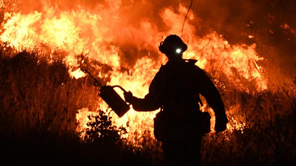 Bomberos llevan a cabo una quema controlada para defender algunas casas contra las llamas del Ranch Fire, parte del complejo de incendios Mendocino, mientras se extendía hacia la ciudad de Upper Lake, California, el 2 de agosto de 2018. Casi 20 grandes incendios han asolado a este estado de Estados Unidos en las últimas dos semanas, avivado por fuertes vientos y altas temperaturas.
