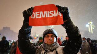 Un manifestant brandissant un panneau demandant la démission du Premier ministre roumain, mercredi 8 février à Bucarest.