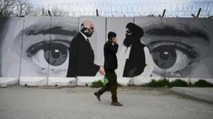 Un homme passe devant une fresque à Kaboul, le 5 avril 2020.