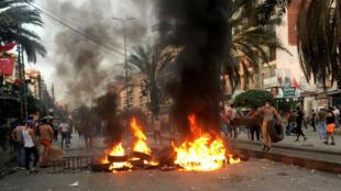 Manifestantes caminan cerca de neumáticos en llamas en Trípoli, Líbano, el 26 de octubre de 2019.