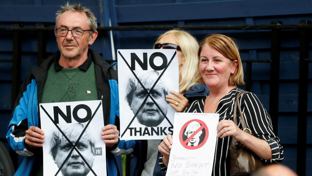 La gente sostiene pancartas contra el primer ministro británico Boris Johnson en una visita a  Edimburgo, Escocia, el 29 de julio de 2019.