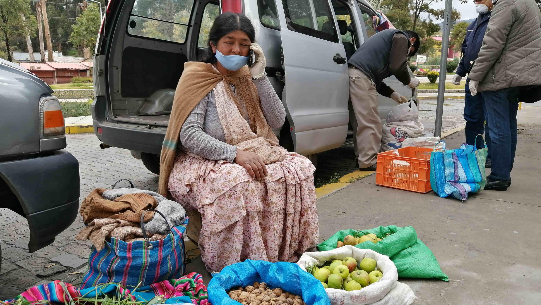 Una mujer habla por teléfono durante un día de entrega de alimentos, vendidos a través de una plataforma móvil, en La Paz, Bolivia, el 17 de abril de 2020.