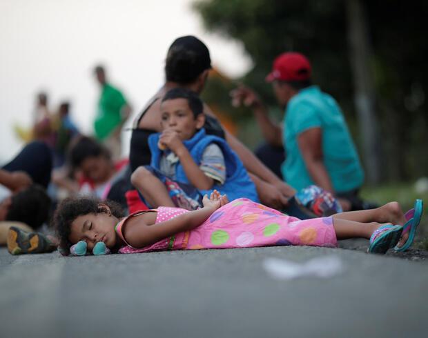 Algunos niños descansan en la carretera mientras viajan con la caravana de miles de migrantes de América Central en ruta a Estados Unidos.