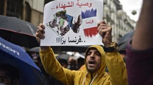 متظاهر جزائري يحمل لافتة خلال تظاهرة للحراك في العاصمة الجزائر بتاريخ 16 نيسان/ابريل 2021