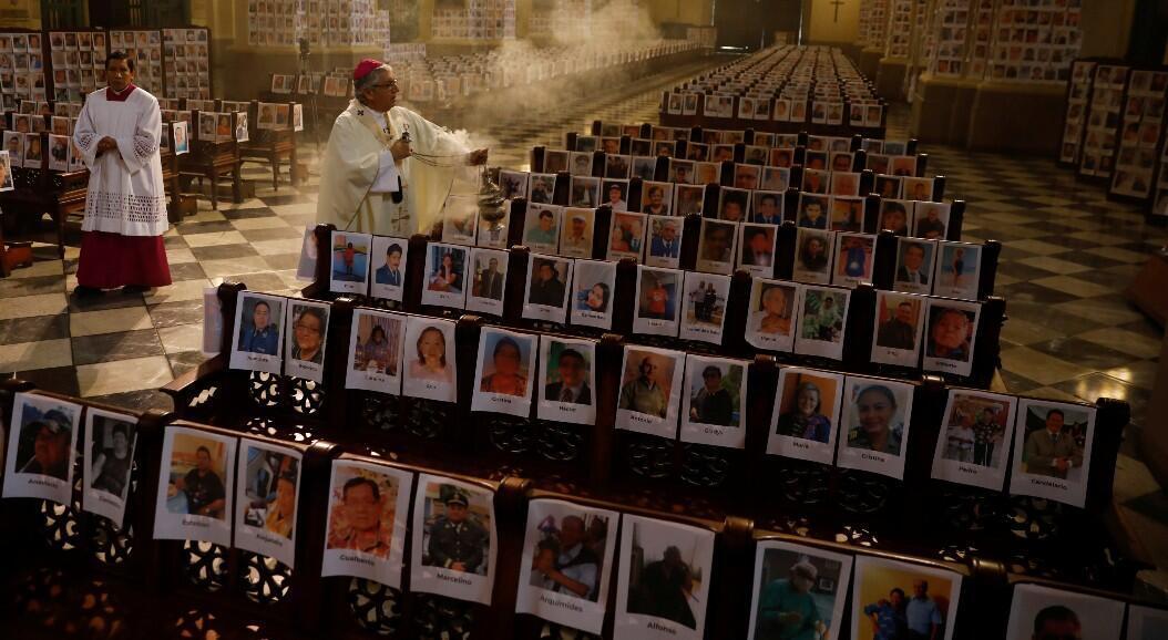 El arzobispo Carlos Castillo bendice con incienso encendido las fotografías de miles de víctimas mortales peruanas por el Covid-19, en la Catedral de Lima, en Lima, Perú, el 14 de junio de 2020.
