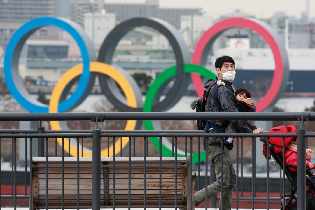 A person wears a face mask against Covid-19 on the Odaiba waterfront in Tokyo with Olympic rings in the background, on January 26, 2021.