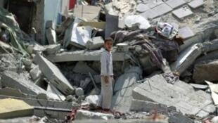 طفل يمني أمام ركام بناء دمرته طائرات التحالف في صنعاء