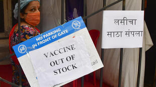 """Une femme se tient à côté d'un panneau portant l'inscription """"Vaccins épuisés"""", à Bombay le 8 avril 2021"""