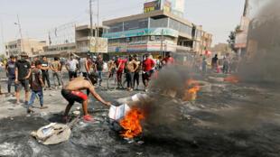 Manifestantes queman neumáticos durante las protestas que desafiaron el toque de queda en Bagdad, Irak, el 3 de octubre de 2019.