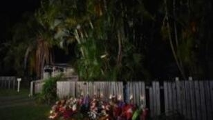 Flowers and stuffed toys are laid opposite the scene where eight children ranging from babies to teenagers were found dead in a house in the northern Australian city of Cairns early on December 20, 2014
