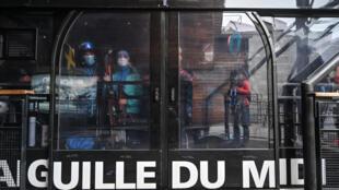 Des skieurs portent des masques de protection dans la cabine du téléphérique de l'Aiguille du Midi, le 16 mai 2020 à Chamonix