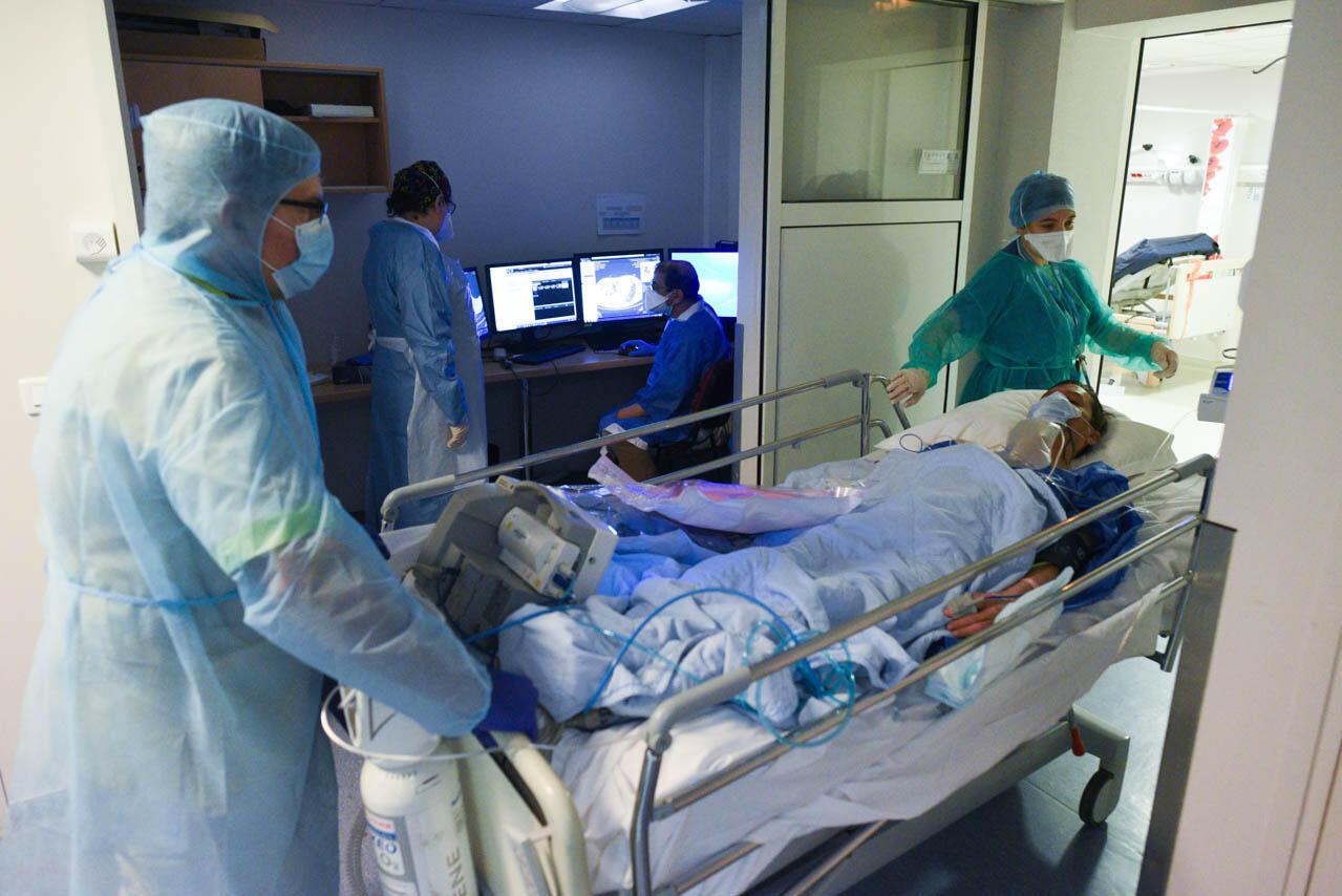 Un patient Covid-19 sur son lit médicalisé pendant son transfert vers la salle du scanner. Un moniteur avec les constantes vitales du patient est visible à ses pieds.