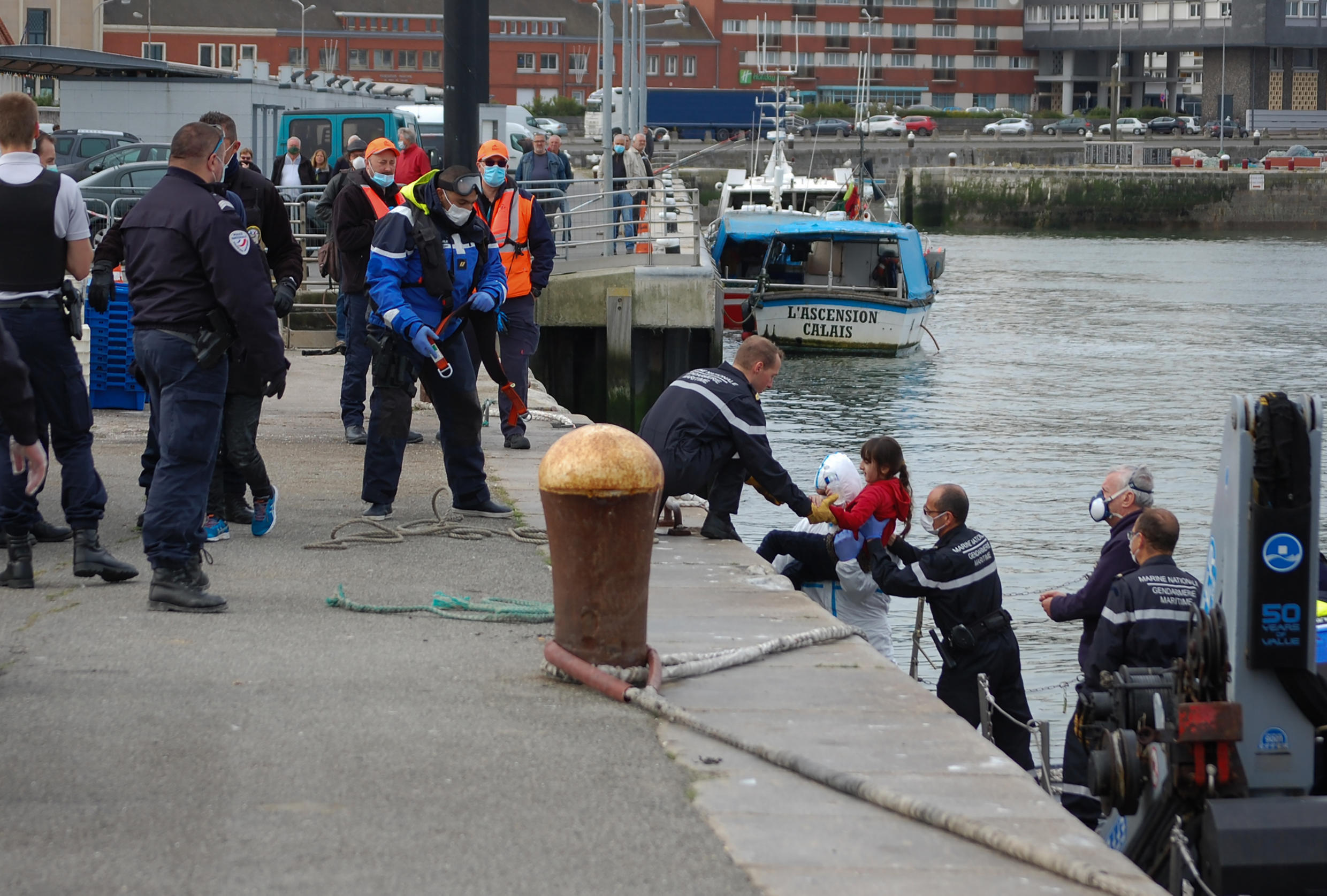 French gendarmes help migrants who failed to cross the English Channel to the UK in May 2020.
