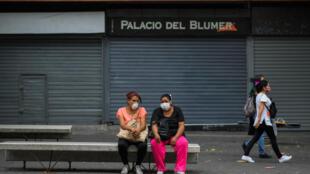 Personas usan máscaras faciales mientras descansan en el bulevar Sabana Grande, en Caracas, el 14 de mayo de 2020 en medio del nuevo brote de coronavirus (COVID-19).