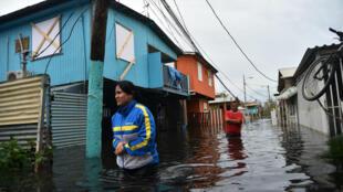Gente camina a través de una calle inundada en Juana Matos, Puerto Rico, el 21 de septiembre de 2017.