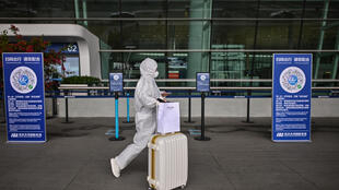 Un passager portant une combinaison de protection et un masque facial passe devant les codes QR de santé de la ville de Wuhan, pour être scanné avant d'entrer dans l'aéroport de Tianhe, dans la province centrale du Hubei en Chine, le 11 avril 2020.