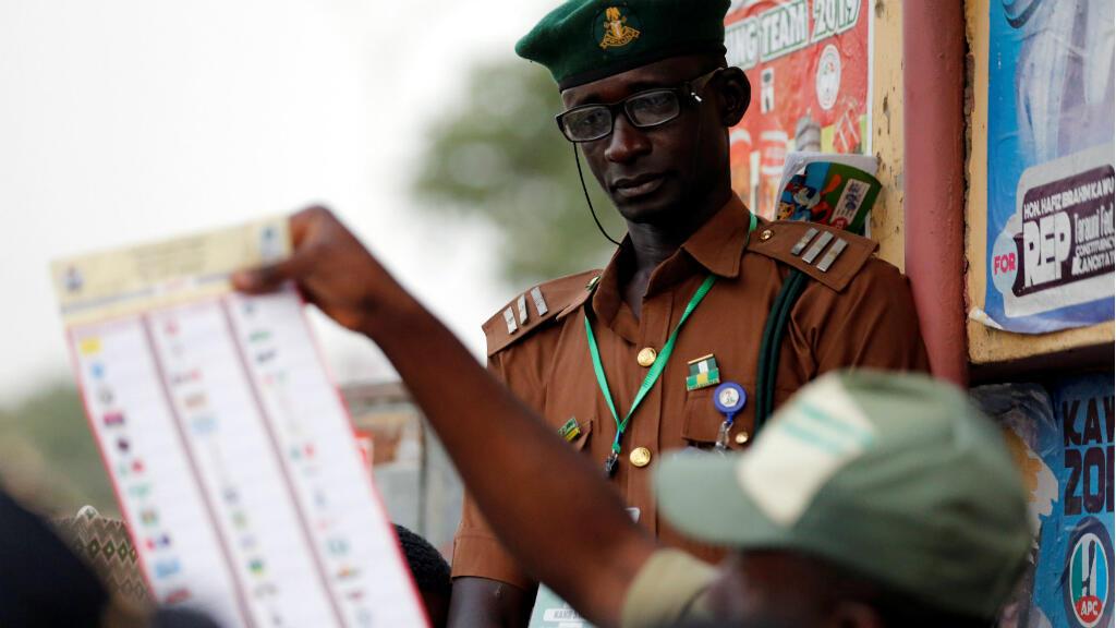 Se ve a un miembro de National Youths Service Corp contando las papeletas electorales después de la votación cerrada en una mesa electoral en el estado de Kano, Nigeria, el 23 de febrero de 2019.