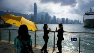 Dos mujeres charlan con el puerto Victoria y el skyline de Hong Kong de fondo en una pasarela junto al agua