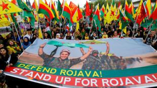 Manifestantes kurdos sostienen pancartas y banderas en una protesta contra la ofensiva militar de Turquía al norte de Siria, en Colonia, Alemania, el 12 de octubre de 2019.