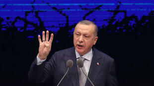 Turkish President Recep Tayyip Erdogan delivers a speech as he stands in front of a huge screen during the Annual Evaluation Meeting for 2019 at the Bestepe National Congress and Culture Center in Ankara on January 16, 2020.