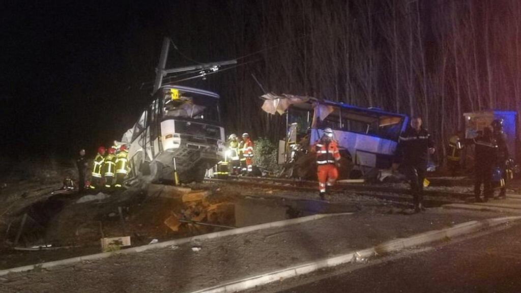 Trabajadores de rescate son vistos en el sitio de colisión entre el tren y el autobús escolar en Millas, Francia, el 14 de diciembre de 2017.