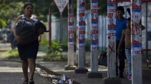 Una mujer camina frente a postes con propaganda política en una calle de Managua, el 3 de noviembre de 2017, durante el inicio del silencio electoral previo a los comicios de este domingo.