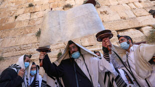 Ultra-Orthodox Jewish men pray at the Western Wall in the Old City of Jerusalem on Sunday, as Israel starts cautiously lifting lockdown restrictions