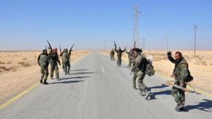 Des soldats des forces gouvernementales syriennes vont le signe de la victoire alors qu'ils approchent des abords de Homs, en février 2017.