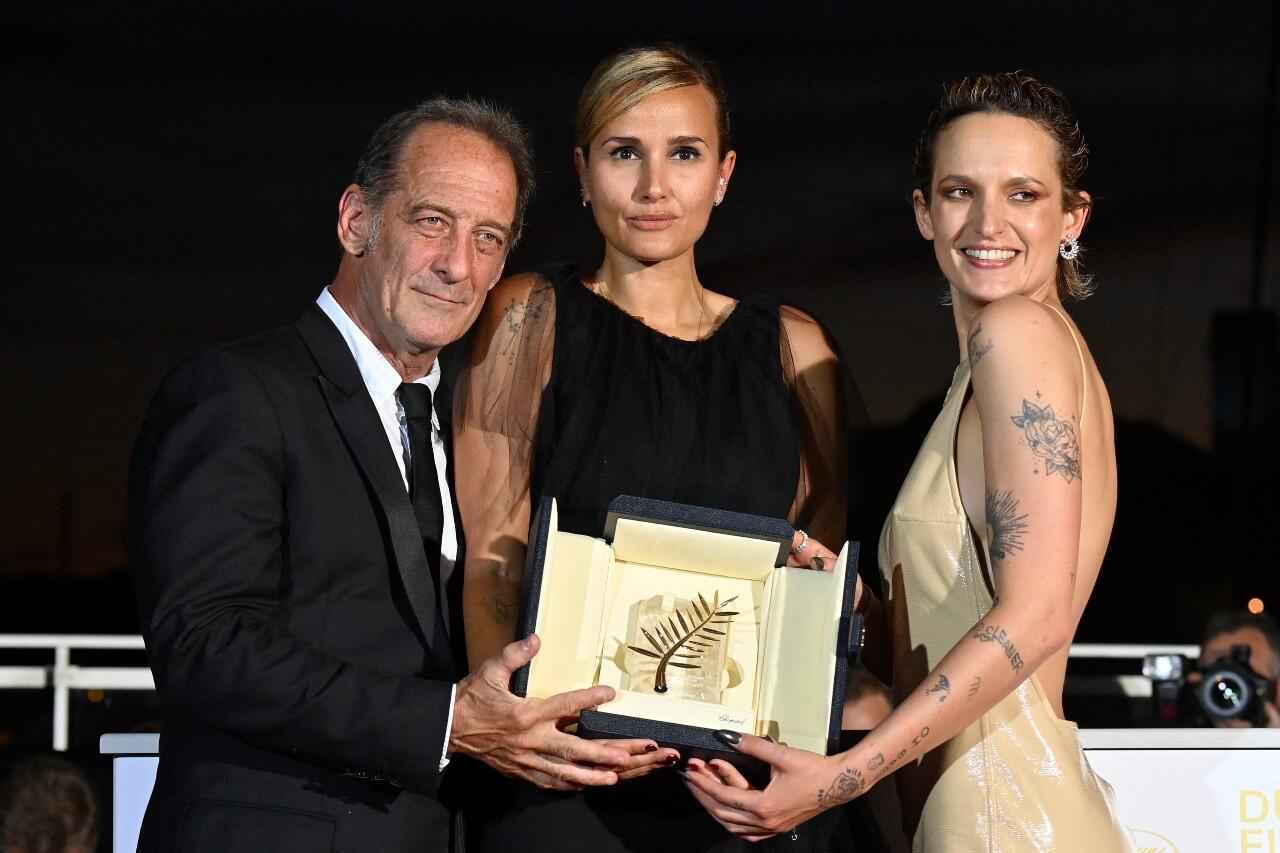 La directora francesa Julia Ducournau (centro) posa junto al actor Vincent Lindon y la actriz Agathe Rousselle, tras recibir la Palma de Oro en Cannes, Francia, el 17 de julio de 2021.