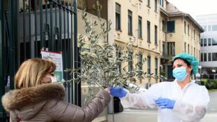 ممرضة في مستشفى مولينيت تتلقى نبتة هدية من امرأة تقديرا لجهودها الطبية، أثناء تفشي فيروس كورونا، في تورينو، إيطاليا ، 5 أبريل/نيسان 2020.