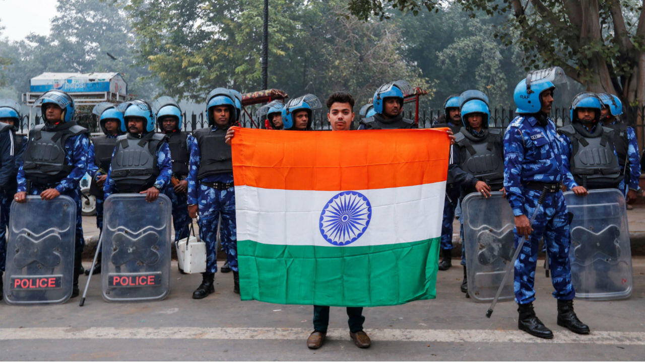Mohammad Anas Qureshi, 20, with the national flag of India in front of riot police during a protest against a new citizenship law in Delhi, India, December 19, 2019.