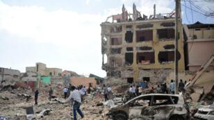 Des passants marchent dans les débris après l'attaque de l'hôtel Dayah par les Shebab, à Mogadiscio, le 25 janvier 2017.