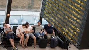 Des vols de la compagnie Ryanair annulés sont affichés dans un terminal de l'aéroport Schoenefeld, à Berlin, où des voyageurs sont endormis, le 10 août 2018.
